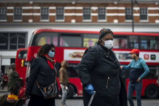 A woman in a protective face mask walks through Brixton Market in South London (Victoria Jones/PA)