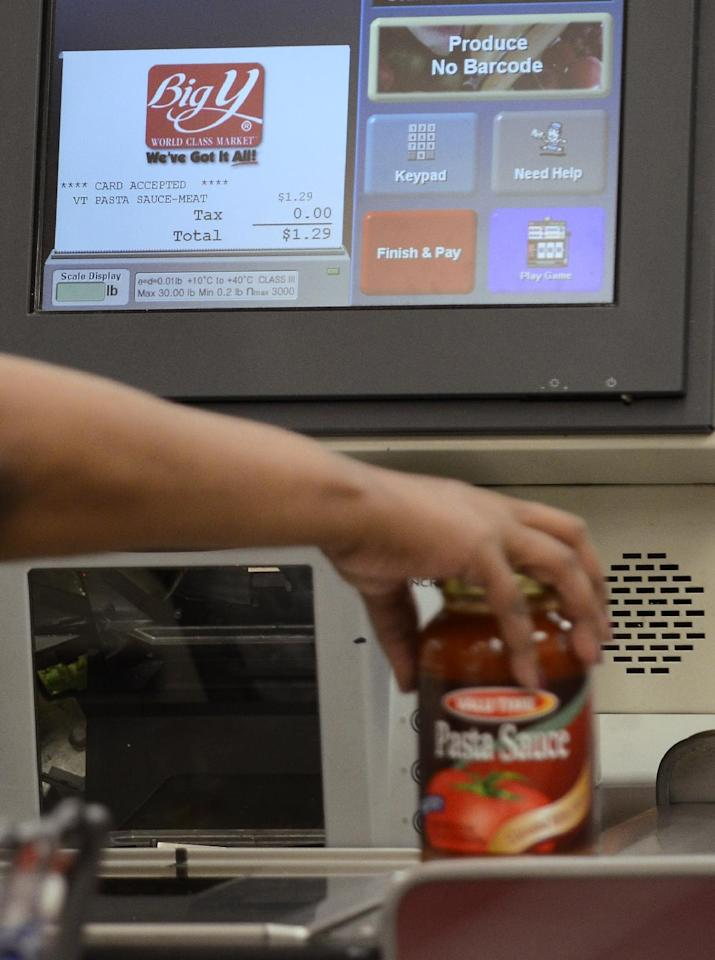 In this Sept. 23, 2011 photo, a customer uses a self-serve checkout station at a Big Y supermarket in Manchester, Conn. A growing number of supermarket chains are bagging their self-serve checkout lanes, saying they can offer better customer service when clerks help shoppers directly. Big Y Foods, which has more than 60 southern New England locations, recently became the latest to announce it's phasing them out. (AP Photo/Jessica Hill)