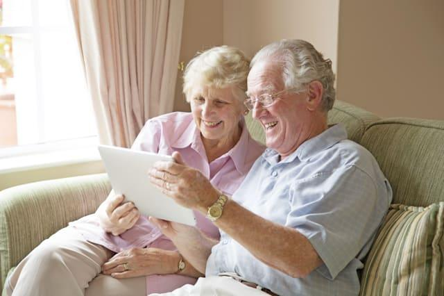 Elderly couple, aged 75-80, looking at photos on a tablet computer in a private retirement home