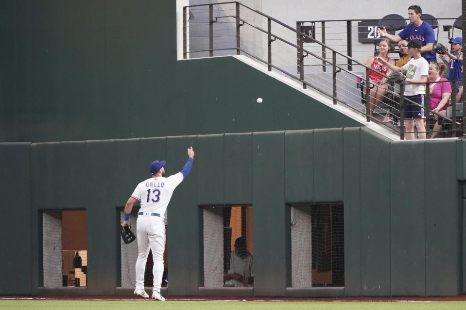 Texas Rangers right fielder Joey Gallo tosses a ball to a fan after catching it in the fifth inning of a baseball game against the Seattle Mariners, Saturday, May 8, 2021, in Arlington, Texas. (AP Photo/Louis DeLuca)