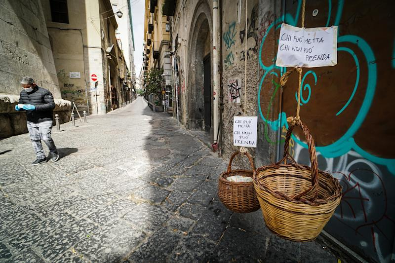 Solidarity baskets with notes reading 'Who can may put, who cannot may take' in one of the deserted streets in the historic center of Naples, southern Italy, on March 30, 2020. | Cesare Abbate—EPA-EFE/Shutterstock