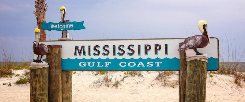 Welcome to Mississippi Gulf Coast sign on sandy beach in Gulfport