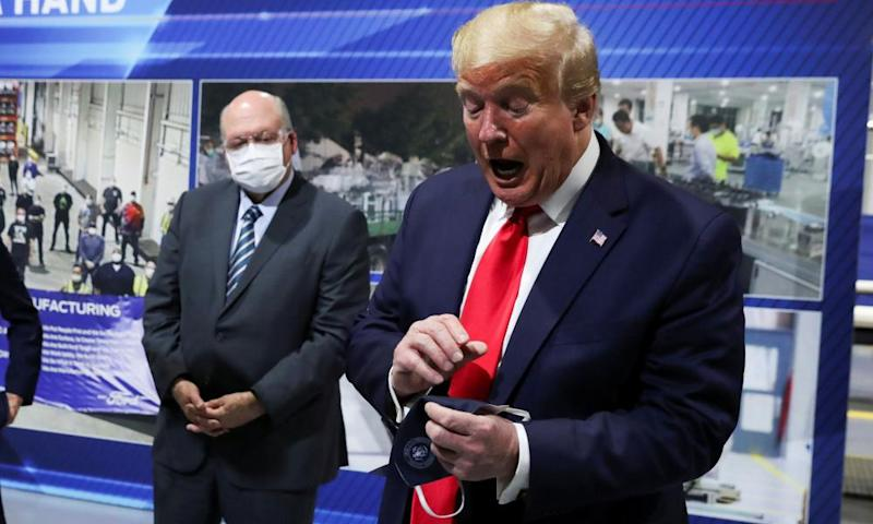 Donald Trump holds a facemask he said he wore during his Ford plant visit.