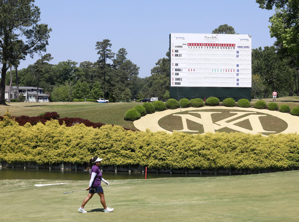 A golfer walks by the leaderboard on the 18th hole during the second round of the LPGA Tour's PureSilk Championship golf tournament Friday, May 21, 2021, in Williamsburg, Va. (Kaitlin McKeown/The Virginian-Pilot via AP)