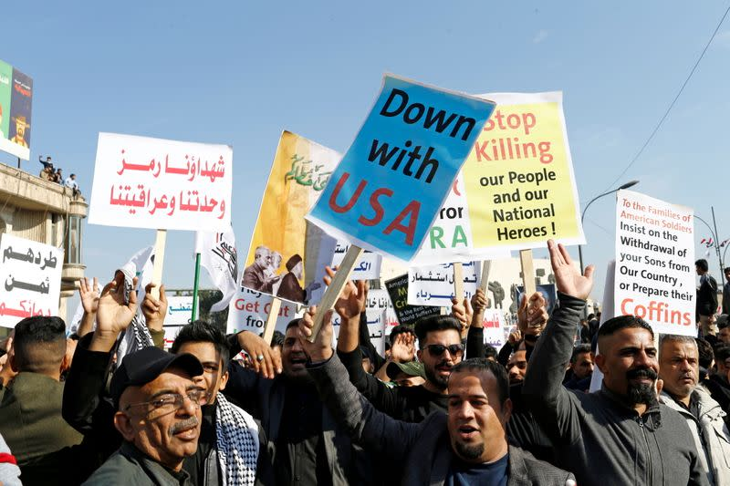 FILE PHOTO: Iraqis, including supporters of Hashid Shaabi (Popular Mobilization Forces), hold placards as they gather to mark the one year anniversary of the killing of senior Iranian military commander General Qassem Soleimani and Iraqi militia commander