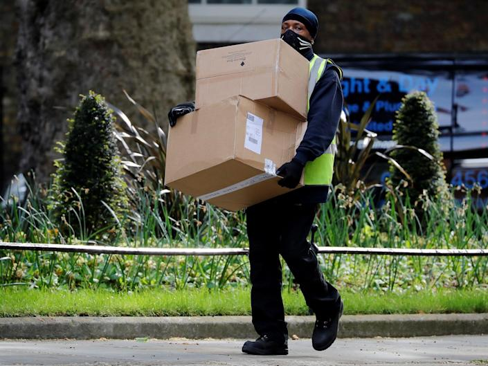 A Hermes delivery courier carries boxes as he makes a delivery to Downing Street: Tolga Akmen/AFP via Getty Images