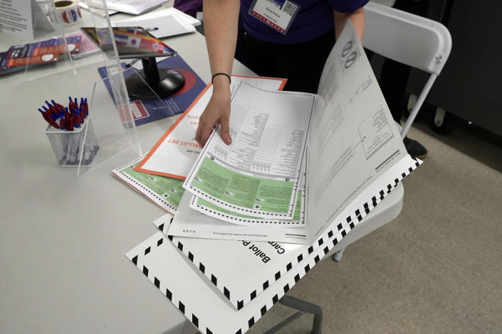 A poll worker assembles a ballot at Frank McCourt High School, in New York, Tuesday, June 22, 2021. The final votes are set to be cast Tuesday in New York's party primaries, where mayors, prosecutors, judges and city and county legislators will be on the ballot, along with other municipal offices. (AP Photo/Richard Drew)