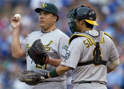 Oakland Athletics starting pitcher Bartolo Colon (21) talks with catcher Kurt Suzuki during the second inning of a baseball game against the Kansas City Royals in Kansas City, Mo., Friday, June 1, 2012. (AP Photo/Orlin Wagner)