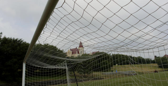 St. Edwards University main building is seen through a soccer goal, Tuesday, May 5, 2020, in Austin, Texas. In response to the economic impact of COVID-19, St. Edwards says they are cutting cut six sports programs including men's and women's tennis, men's and women's golf and men's soccer. (AP Photo/Eric Gay)
