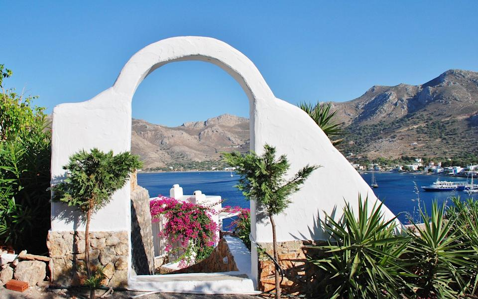 A white archway frames Livadia harbour on Tilos - iStock Editorial