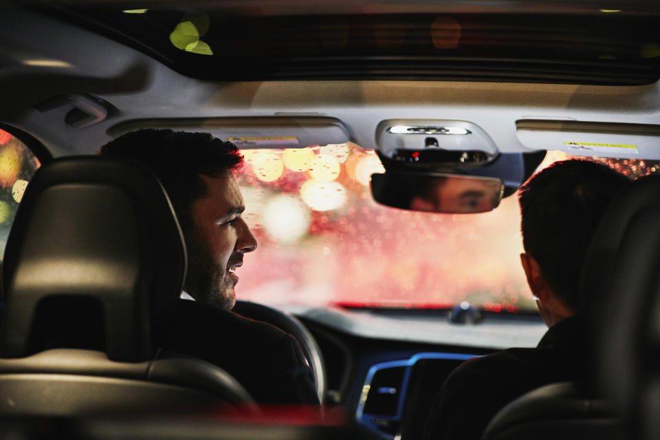Two businessmen in discussion in car while waiting in rush hour traffic
