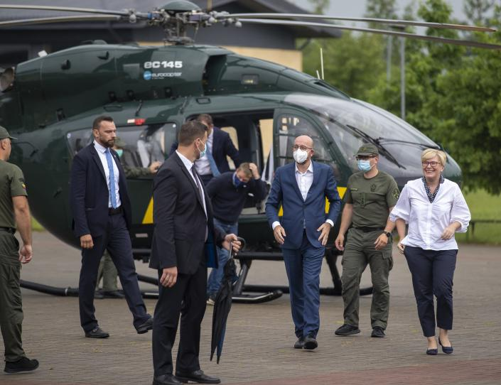 European Council President Charles Michel, center, and Lithuania's Prime Minister Ingrida Simonyte, right, arrive at the place of the Lithuania State Border Guard on the Lithuanian-Belarusian border, near the village Padvarionys, some 40km (24 miles) east of the capital Vilnius, Lithuania, Tuesday, July 6, 2021. (AP Photo/Mindaugas Kulbis)