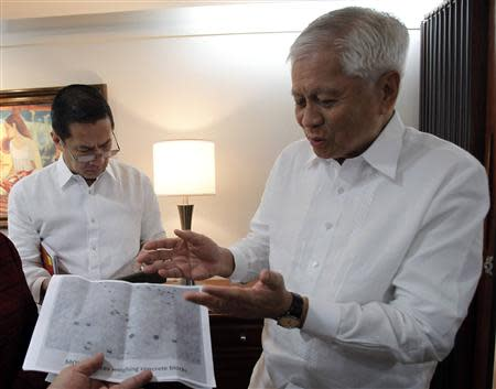 Philippine Foreign Affairs Secretary Albert Del Rosario looks at an aerial handout photograph from the Ministry of Defense showing concrete blocks from China on the disputed Scarborough Shoal in the South China Sea, represented by the dark spots on the photograph, during a Reuters interview at the Department of Foreign Affairs headquarters in Manila September 4, 2013. REUTERS/Romeo Ranoco