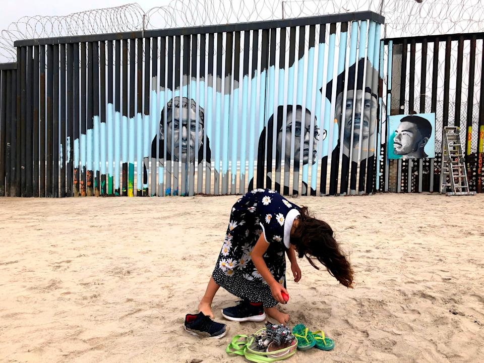A girl stands near a new mural which has been painted on the Mexican side of a border wall in Tijuana, Mexico.