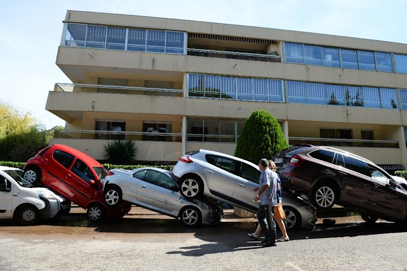 People pass cars stacked onto one another on October 4, 2015, in Mandelieu-la-Napoule, southeastern France (AFP Photo/Boris Horvat)