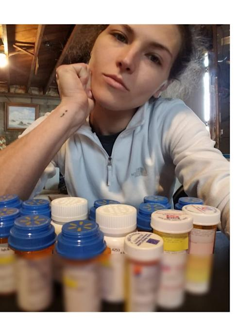 A photo of a woman in front of 14 pill bottles, looking straight into the camera. The pill bottle labels are blurred out.