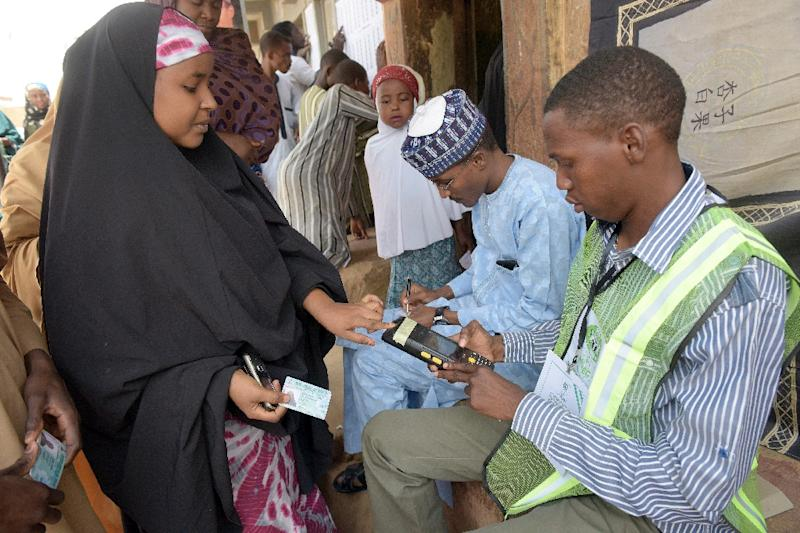 A woman is accredited to vote by a biometric system on March 28, 2015 outside a polling station in Gidan Niyam Sakin Yara in Daura in Katsina State (AFP Photo/Pius Utomi Ekpei)