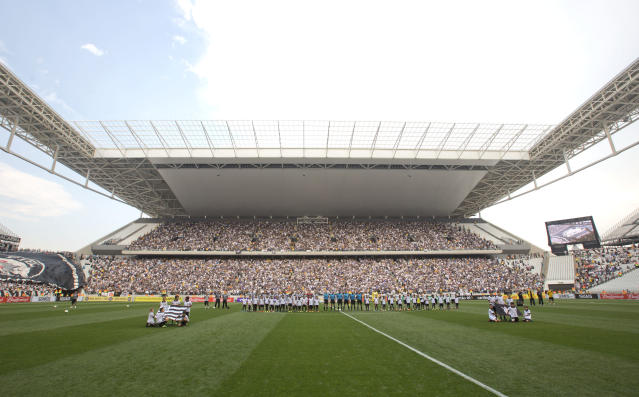 Corinthians's and Figueirense players listen to the national anthem prior to a Brazilian soccer league match at the Itaquerao, the still unfinished stadium that will host the World Cup opener match between Brazil and Croatia on June 12, in Sao Paulo, Brazil, Sunday, May 18, 2014. Only 40,000 tickets were put on sale for Corinthians' match against Figueirense because some of the 20,000 temporary seats needed for the World Cup opener are still being installed. (AP Photo/Andre Penner)