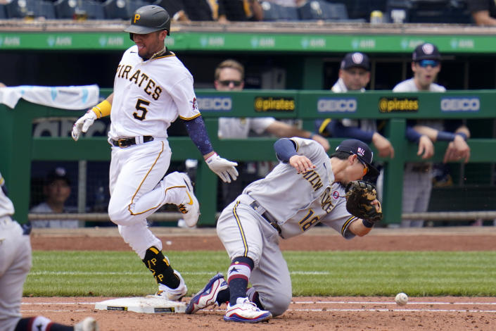 Pittsburgh Pirates' Michael Perez (5) reaches first safely as Milwaukee Brewers second baseman Keston Hiura cannot handle an errant toss by pitcher Freddy Peralta during the fourth inning of a baseball game in Pittsburgh, Sunday, July 4, 2021. (AP Photo/Gene J. Puskar)
