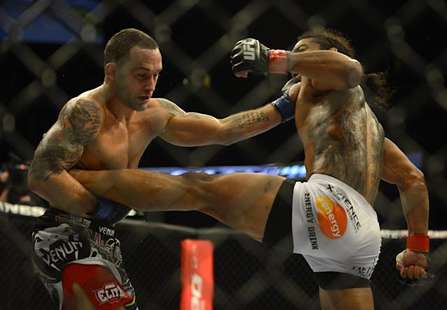 Benson Henderson from Arizona receives a punch to the chin while having his leg held by Frankie Edgar from New Jersey in their middleweight title bout during UFC 150 in Denver, Saturday, Aug. 11, 2012. Henderson won the bout.(AP Photo/Jack Dempsey)