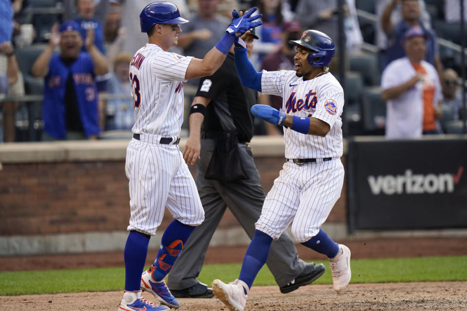 New York Mets' James McCann, left, celebrates with teammate Francisco Lindor, right, after Lindor scored the winning run on a single by Dominic Smith during the eighth inning of the first baseball game of a doubleheader against the Philadelphia Phillies, Friday, June 25, 2021, in New York. (AP Photo/Frank Franklin II)