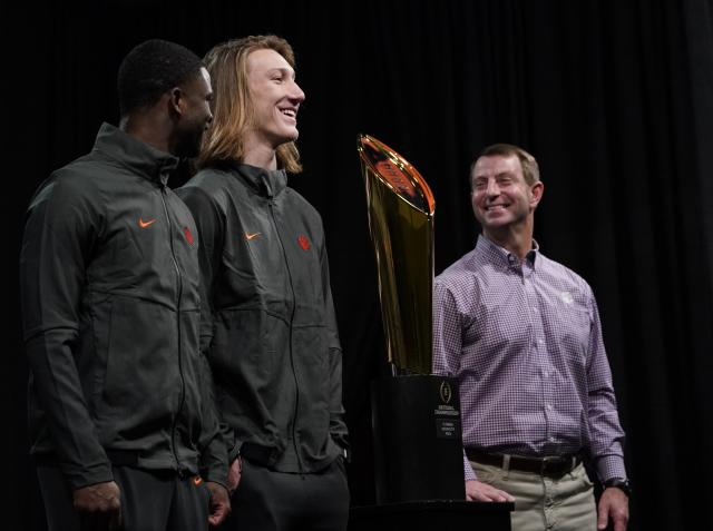 Clemson head coach Dabo Swinney, Trevor Lawrence and Trayvon Mullen pose with the championship trophy at a news conference for the NCAA college football playoff championship game Tuesday, Jan. 8, 2019, in San Jose, Calif. (AP Photo/Morry Gash)