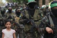 A girl looks on as members of Al-Qassam brigades, the armed wing of the Palestinian Hamas group, march in Gaza City on May 22 in commemoration of senior Hamas commander Bassem Issa who was killed in am Israeli airstrike