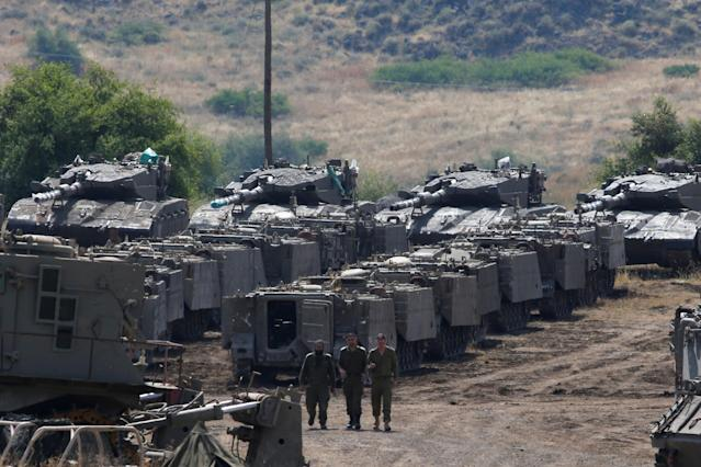 <p>Israeli soldiers walk among armored vehicles in the Israeli-occupied Golan Heights, Israel, May 10, 2018. (Photo: Ronen Zvulun/Reuters) </p>