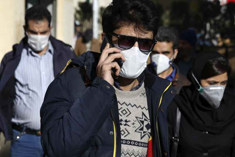 A man wearing a face mask speaks on his cellphone, in downtown Tehran, Iran, Monday, March 2, 2020. A member of a council that advises Iran's supreme leader died Monday after falling sick from the new coronavirus, becoming the first top official to succumb to the illness striking both citizens and leaders of the Islamic Republic. (AP Photo Vahid Salemi)