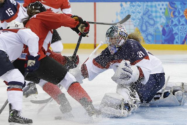 Rebecca Johnston of Canada takes a shot at the goal as USA Goalkeeper Jessie Vetter reaches for the puck during the second period of the 2014 Winter Olympics women's ice hockey game at Shayba Arena, Wednesday, Feb. 12, 2014, in Sochi, Russia. (AP Photo/Matt Slocum)