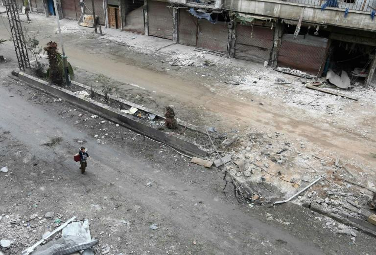 A Syrian child walks past debris in Eastern Ghouta on February 22, 2018