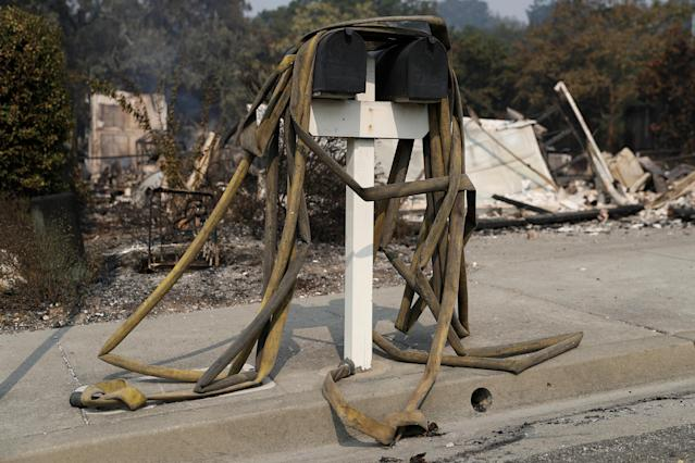 <p>Water hoses are seen on a post box at a neighborhood destroyed by the Tubbs Fire in Santa Rosa, Calif., Oct. 10, 2017. (Photo: Stephen Lam/Reuters) </p>