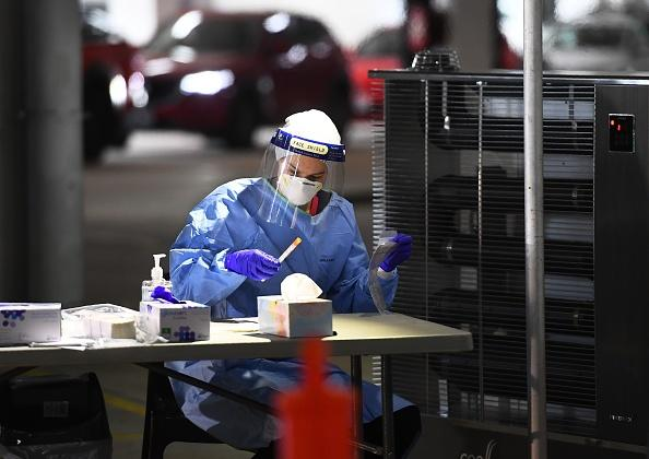 Medical staff take down details after performing tests for the COVID-19 coronavirus on people who used a drive-through testing site in a Melbourne carpark.