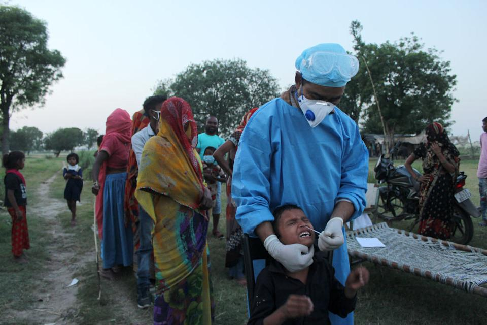 A health worker in personal protective equipment (PPE) collects a nasal swab.