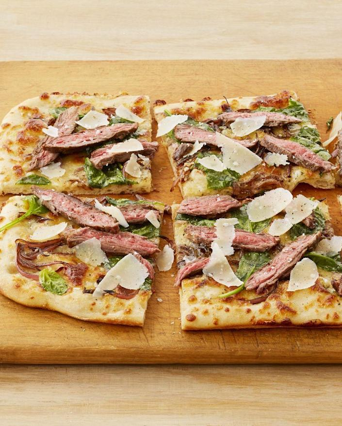 """<p>Weeknight dinner doesn't have to be complicated! Store-bought pizza dough and extra slices of steak make this meal super easy. </p><p><a href=""""https://www.thepioneerwoman.com/food-cooking/recipes/a32391909/steakhouse-pizza-with-blue-cheese-recipe/"""" rel=""""nofollow noopener"""" target=""""_blank"""" data-ylk=""""slk:Get Ree's recipe."""" class=""""link rapid-noclick-resp""""><strong>Get Ree's recipe. </strong></a></p><p><a class=""""link rapid-noclick-resp"""" href=""""https://go.redirectingat.com?id=74968X1596630&url=https%3A%2F%2Fwww.walmart.com%2Fsearch%2F%3Fquery%3Dbaking%2Bsheet&sref=https%3A%2F%2Fwww.thepioneerwoman.com%2Ffood-cooking%2Frecipes%2Fg37180949%2Fleftover-steak-recipes%2F"""" rel=""""nofollow noopener"""" target=""""_blank"""" data-ylk=""""slk:SHOP BAKING SHEETS"""">SHOP BAKING SHEETS</a></p>"""