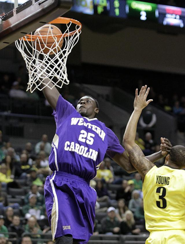 Western Carolina guard James Sinclair,left, goes to the basket against Oregon guard Joseph Young during the first half of an NCAA college basketball game in Eugene, Ore., Wednesday, Nov. 13, 2013. (AP Photo/Don Ryan)