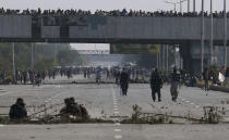 Supporters of 'Tehreek-e-Labaik Pakistan, a religious political party, block a main highway during an anti-France rally in Islamabad, Pakistan, Monday, Nov. 16, 2020. The supporters are protesting the French President Emmanuel Macron over his recent statements and the republishing in France of caricatures of the Muslim Prophet Muhammad they deem blasphemous. (AP Photo/Anjum Naveed)
