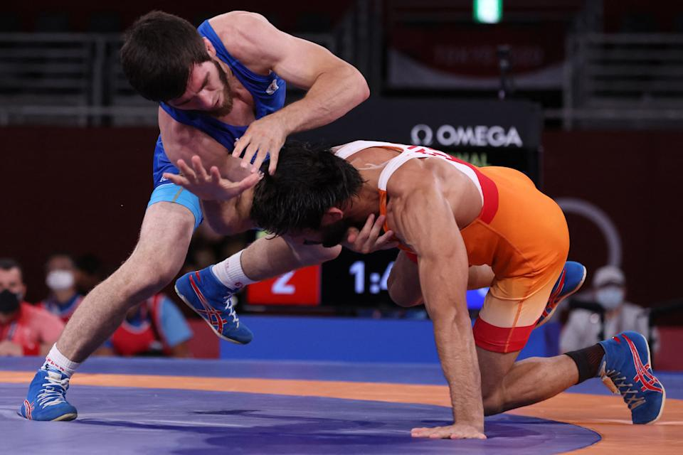 Russia's Zavur Uguev (blue) wrestles India's Kumar Ravi in their men's freestyle 57kg wrestling final match during the Tokyo 2020 Olympic Games at the Makuhari Messe in Tokyo on August 5, 2021. (Photo by Jack GUEZ / AFP) (Photo by JACK GUEZ/AFP via Getty Images)