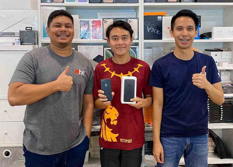 Phone seller Muhammad Asyraf Ab Rahim (left) decided to give Hafizuddin Gos Hambali (centre) a brand new gadget after reading about his academic achievements online. — Picture from Twitter/hafizuddingh