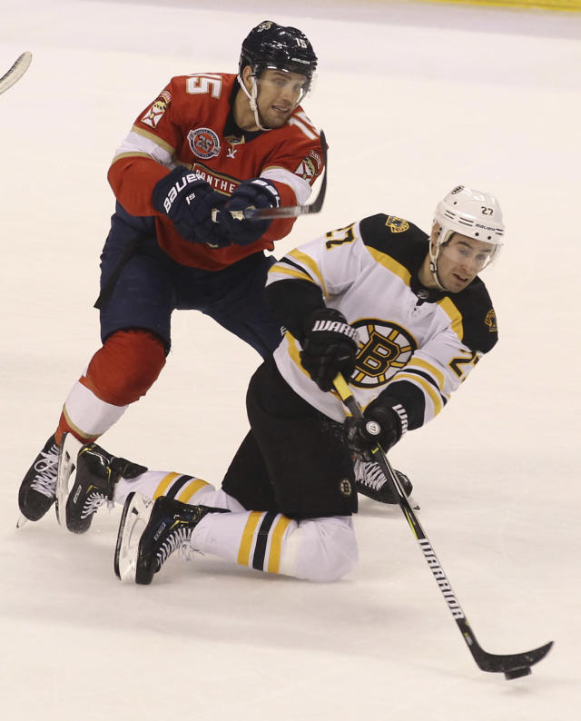 Boston Bruins' John Moore, right, passes the puck as Florida Panthers' Riley Sheahan, left, defends during the first period of an NHL hockey game, Saturday, March 23, 2019, in Sunrise, Fla. (AP Photo/Luis M. Alvarez)