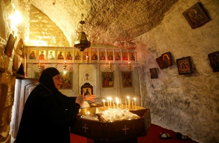 A nun lights candles in the Syrian village of Maalula, in of the world's oldest Christian settlements