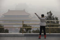 A visitor stretches her arms as she looks over the Forbidden City through severe haze in Beijing Sunday, Jan. 13, 2013. People refused to venture outdoors and buildings disappeared into Beijing's murky skyline on Sunday as the capital's air quality went off the index. (AP Photo/Ng Han Guan)