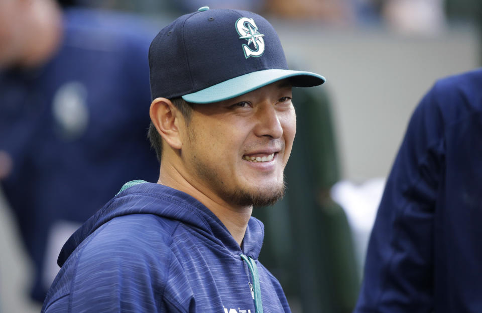 Seattle Mariners pitcher Hisashi Iwakuma smiles as he greets teammates in the dugout before the team's baseball game against the Oakland Athletics, Friday, July 7, 2017, in Seattle. (AP Photo/Ted S. Warren)