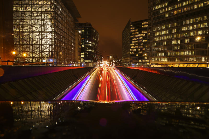 In this photo taken with a slow shutter speed, commuters drive between Europa, left, and European Commission buildings, right, both European Union headquarters in Brussels, Monday, Nov. 18, 2019. (AP Photo/Francisco Seco)