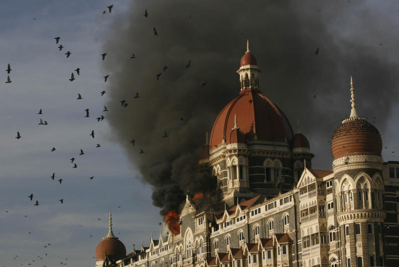 FILE - In this Nov. 27, 2008, file photo, pigeons fly as the Taj Hotel continues to burn from an attack that killed multiple people in Mumbai, India. Tahawwur Rana, a Pakistani-born Canadian, was convicted of a crime related to the Mumbai killings that are sometimes called India's 9/11, though U.S. prosecutors had failed to prove a terrorism charge that connected him directly to the three-day rampage during his 2011 trial. The Chicago businessman who spent more than 10 years in prison for supporting terrorist groups has now been arrested in Los Angeles to face charges in India for attacks in Mumbai in 2008 that killed more than 160 people, U.S. prosecutors said Friday, June 19, 2020. (AP Photo/Gautam Singh, File)