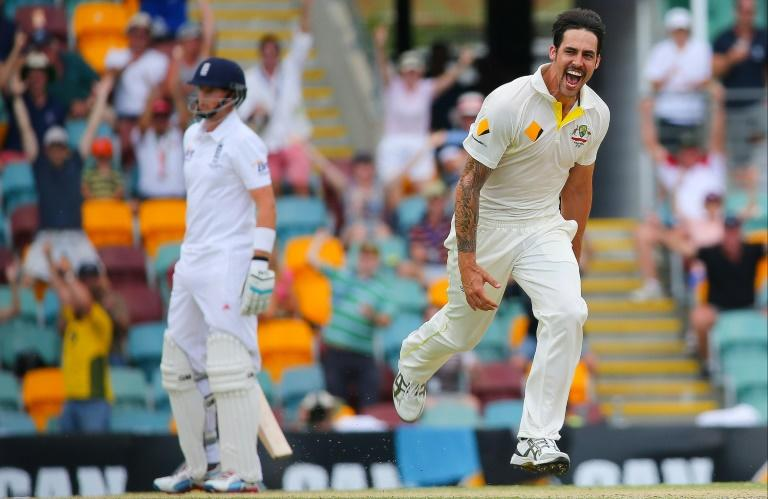 Pace bowler Mitchell Johnson celebrates the fall of Stuart Broad as current England captain Joe Root looks on from the non-striker's at the Gabba on the last Ashes tour in 2013