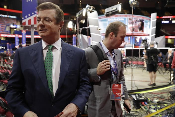Trump Campaign Chairman Paul Manafort talks to reporters on the floor of the Republican National Convention at Quicken Loans Arena in Cleveland as Rick Gates listens at back right on July 17, 2016. (Photo: Matt Rourke/AP)