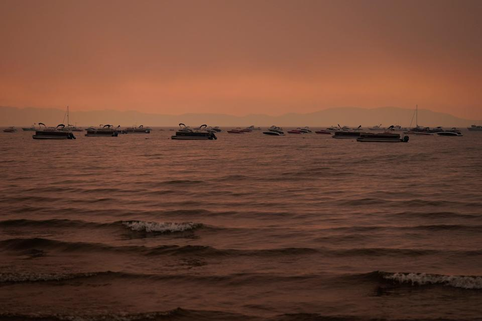 Boats float in the water away from a dock in South Lake Tahoe, Calif., as the Caldor Fire approaches Lake Tahoe.