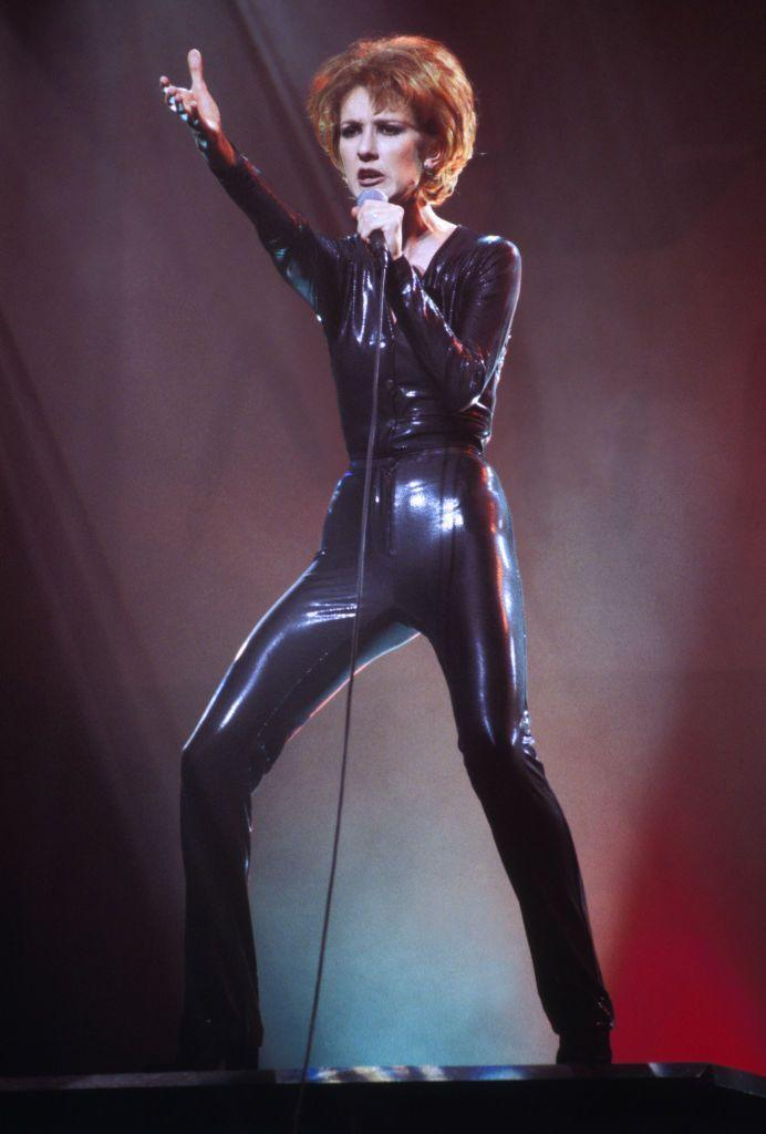 <p>An admirable quality of Dion's style is how versatile it is. She goes from angelic to edgy in a pinch, and nobody questions it. Here, she chose a skintight black synthetic catsuit for a performance in France. </p>