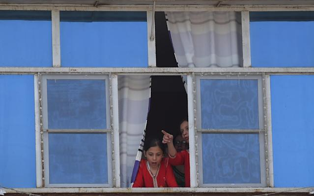 <p>Afghan girls look at the site of a suicide attack through a window of their building in Kabul on Aug. 29, 2017. (Photo: Shah Marai/AFP/Getty Images) </p>